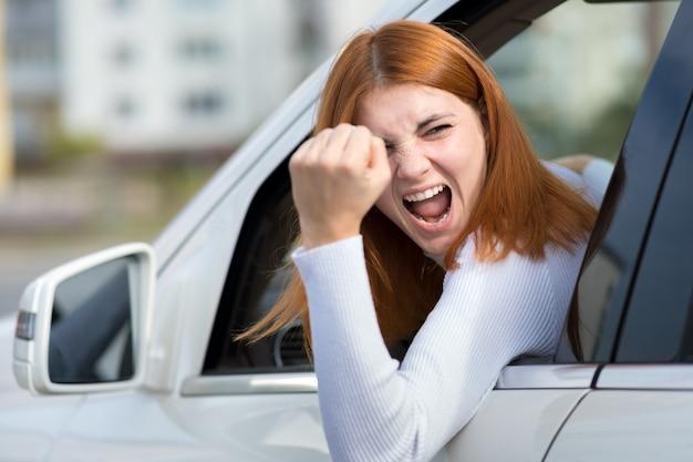 Closeup retrato de irritado descontente mulher agressiva com raiva, dirigindo um carro gritando com alguém com mão punho acima. conceito de expressão humana negativa