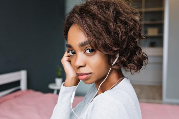 Closeup retrato de jovem africana com cabelo curto e encaracolado, ouvindo música em fones de ouvido, olhar sério, quarto. vestindo camiseta cinza claro com mangas compridas.