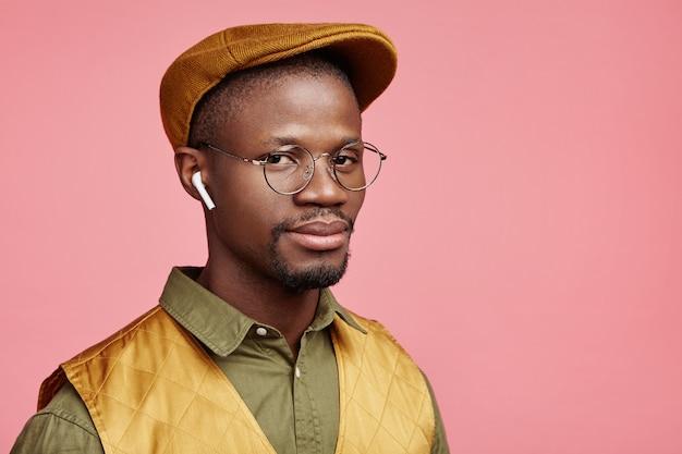 Closeup retrato de jovem afro-americano com chapéu e fones de ouvido sem fio