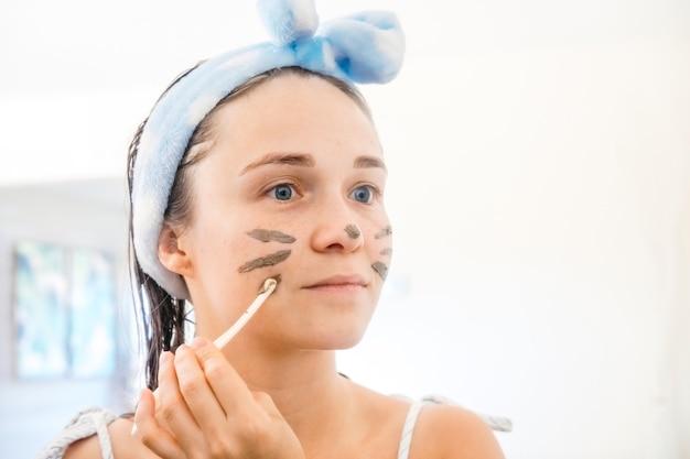 Closeup retrato de jovem aplicando máscara de café para limpeza facial e tratamento de spa