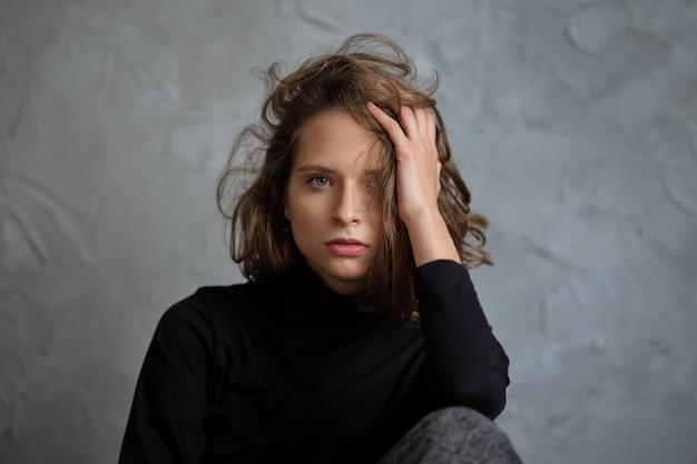 Closeup retrato de jovem apoiando a cabeça com o braço