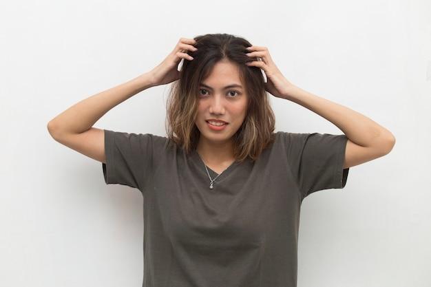 Closeup retrato de jovem asiática coçando a cabeça com a mão