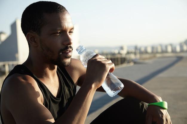 Closeup retrato de jovem barbudo bebendo água
