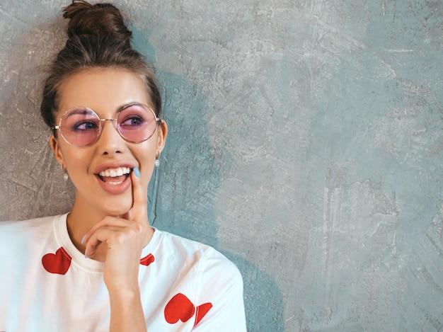 Closeup retrato de jovem bela mulher sorridente olhando. menina na moda em verão casual branco vestido e óculos de sol. . pensando