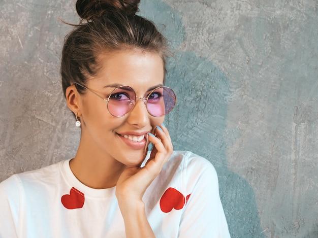 Closeup retrato de jovem bela mulher sorridente olhando. menina na moda em verão casual branco vestido e óculos de sol.