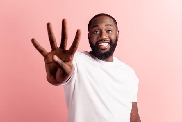 Closeup retrato de jovem bonito fazendo um sinal de quatro dedos na parede rosa