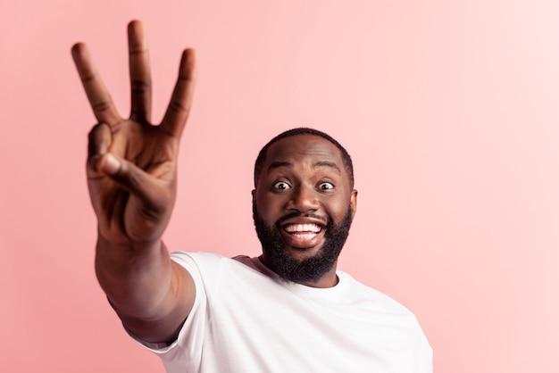 Closeup retrato de jovem bonito fazendo um sinal de três dedos