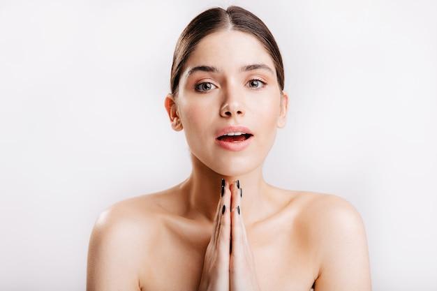 Closeup retrato de jovem com rosto perfeitamente limpo sem maquiagem, mãos postas em gesto de oração na parede branca.