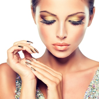 Closeup retrato de jovem com uma maquiagem chique para a noite, cílios grandes e esmalte dourado