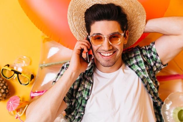 Closeup retrato de jovem de óculos laranja e chapéu de palha. homem de camiseta está descansando no colchão inflável e falando ao telefone.