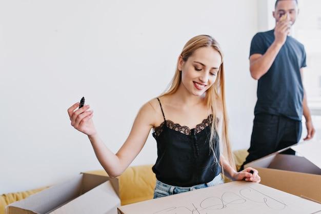 Closeup retrato de jovem embalando caixas, etiquetando a caixa de papelão com livros, mudando-se de casa nova, apartamento. casal feliz se mudando.