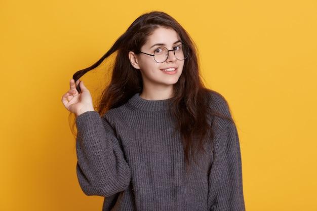 Closeup retrato de jovem morena tocando o cabelo dela, vestindo blusa preta e óculos arredondados