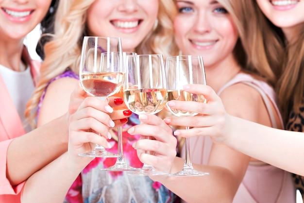 Closeup retrato de jovens mulheres felizes em festa e bebendo vinho - isolado no branco