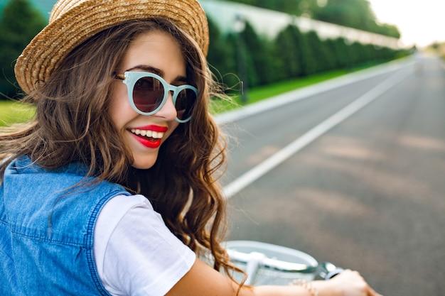 Closeup retrato de linda garota com cabelo longo cacheado no chapéu, dirigindo uma bicicleta na estrada. ela usa gibão e óculos de sol azuis. ela está sorrindo para a câmera, vista de trás.