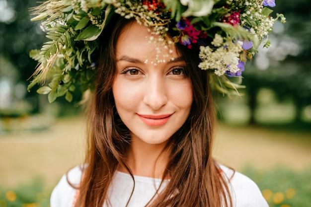 Closeup retrato de linda jovem com coroa de flores na cabeça dela.