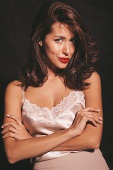 Closeup retrato de linda mulher morena sensual. garota com roupas clássicas bege elegantes. modelo com os lábios vermelhos isolados no preto