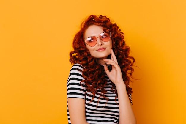 Closeup retrato de menina adorável pensativa com cabelo ruivo ondulado, vestindo camiseta e óculos em forma de coração.