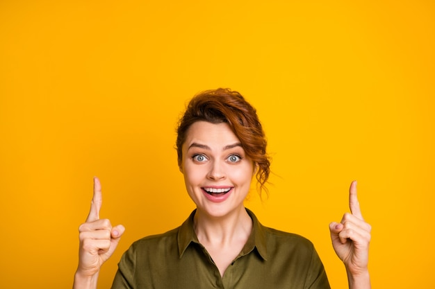 Closeup retrato de menina alegre apontando dois indicadores para cima do espaço da cópia