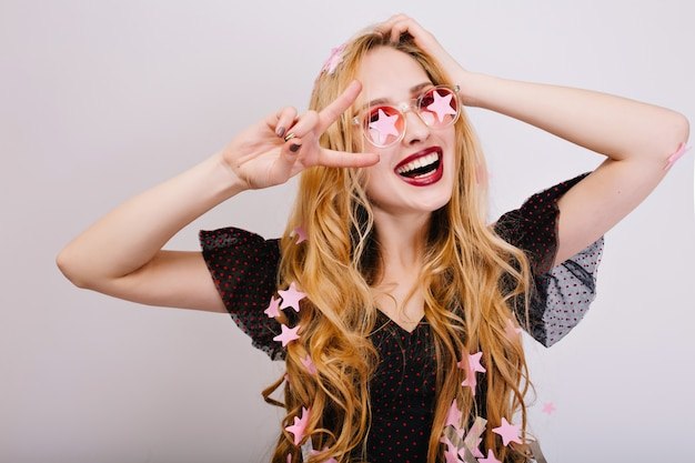 Closeup retrato de menina alegre com cabelo loiro encaracolado, se divertindo muito na festa, se divertindo, comemorando, mostrando paz. ela está usando um vestido preto, óculos rosa elegantes. isolado..
