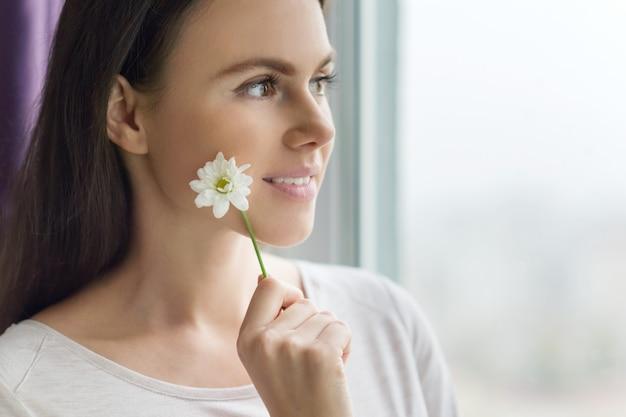 Closeup retrato de menina com flor de camomila