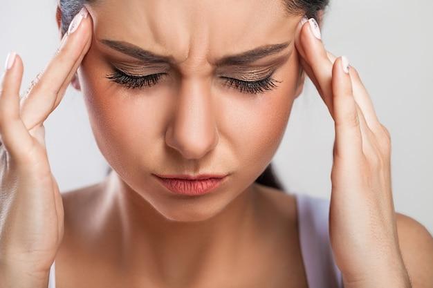 Closeup retrato de menina doente bonita sofrendo de dor de cabeça