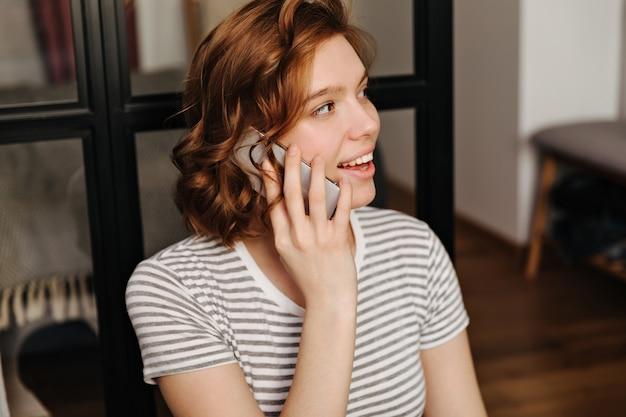 Closeup retrato de menina encaracolada vermelha em t-shirt listrada, falando no telefone.