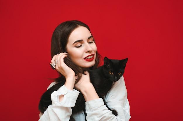 Closeup retrato de menina feliz abraçando o gato preto a