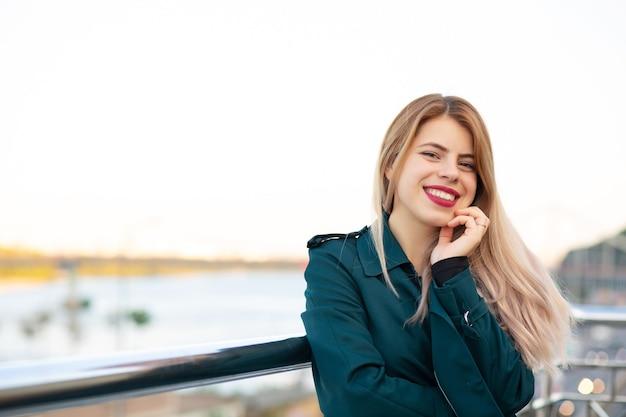Closeup retrato de menina loira alegre, vestindo um casaco verde. espaço para texto