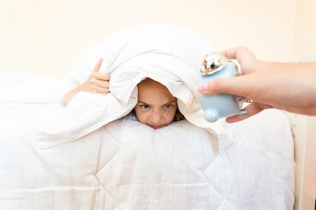 Closeup retrato de mulher acordando garota com despertador no início da manhã