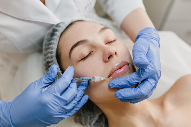Closeup retrato de mulher bonita durante a terapia de cosmetologia no salão de beleza. botox, lábios, injeção, procedimentos profissionais, levantamento, rejuvenescimento, dispositivos modernos, saúde