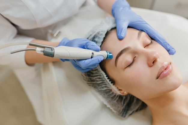 Closeup retrato de mulher bonita durante a terapia de cosmetologia no salão de beleza. procedimentos profissionais de dermatologia, levantamento, rejuvenescimento, dispositivos modernos, saúde