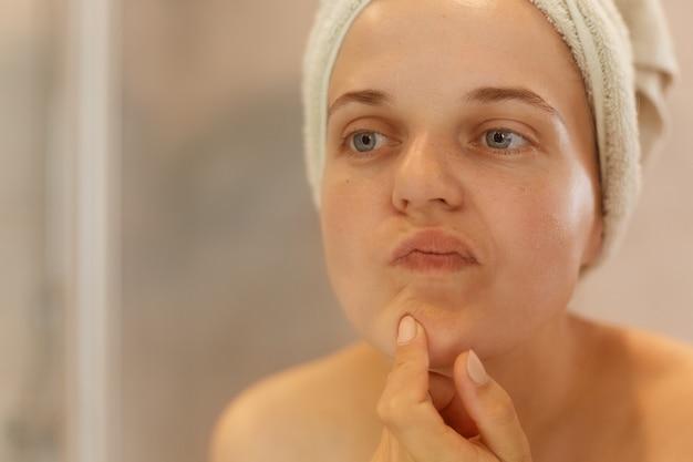 Closeup retrato de mulher bonita olhando para o rosto dela, tentando encontrar acne, posando com ombros nus e toalha na cabeça, fazendo procedimentos de beleza matinais.