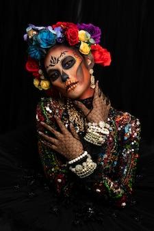 Closeup retrato de mulher com uma maquiagem de caveira de açúcar vestida com coroa de flores.