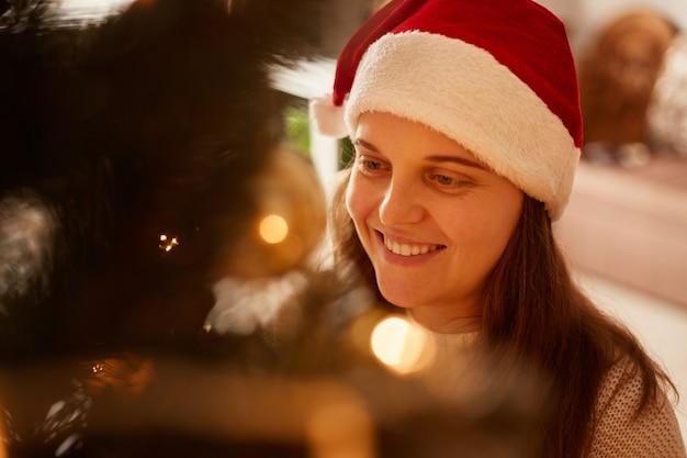Closeup retrato de mulher de cabelos escuros de natal se passando perto das luzes da árvore de natal, tendo uma expressão facial feliz, olhando para longe, a celebração da véspera de ano novo.