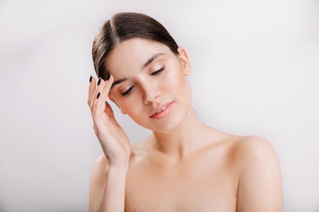 Closeup retrato de mulher envergonhada com rosto limpo e bonito, sem maquiagem na parede isolada.