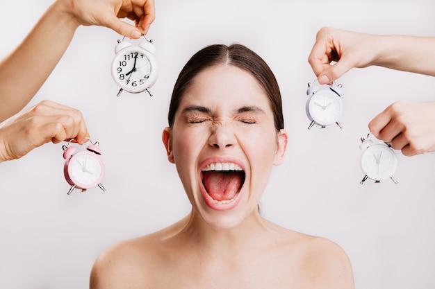 Closeup retrato de mulher jovem gritando emocionalmente contra uma parede branca com despertadores.