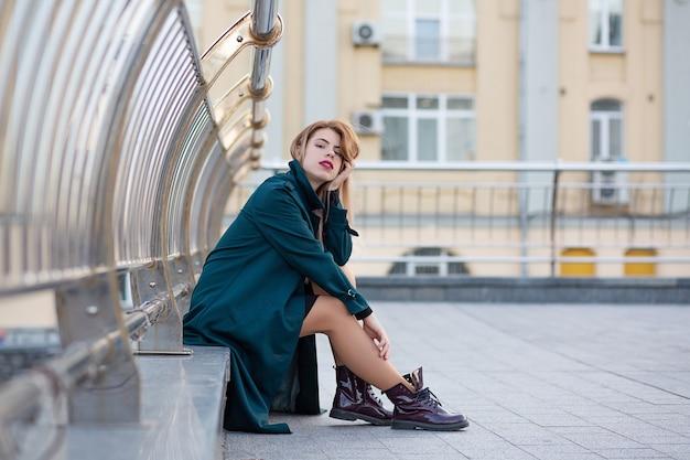Closeup retrato de mulher loira elegante, vestindo um casaco verde, sentado perto do corrimão. espaço para texto