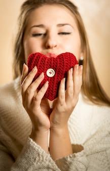 Closeup retrato de mulher mandando beijo e coração vermelho
