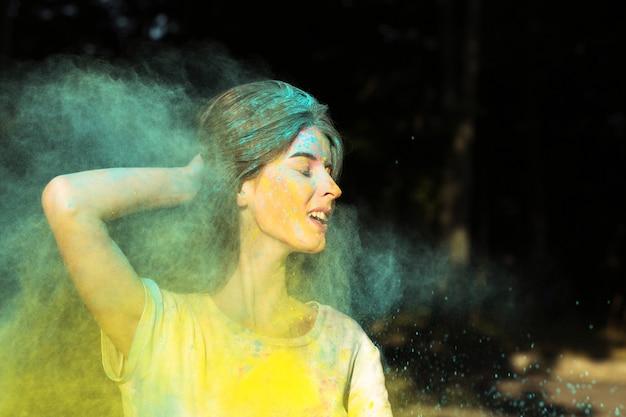 Closeup retrato de mulher morena sorridente brincando com tinta amarela e verde seca holi