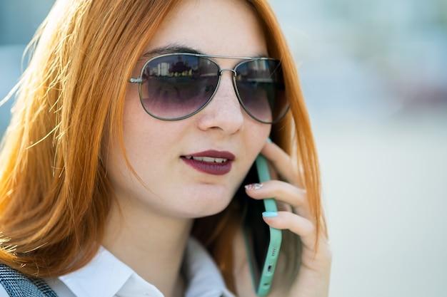 Closeup retrato de mulher ruiva jovem elegante em óculos de sol, falando no celular ao ar livre no verão.
