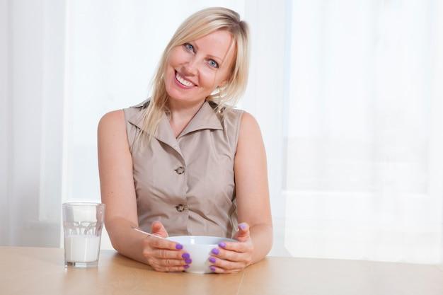 Closeup retrato de mulher segurando o copo com iogurte orgânico com sementes de coco e chia.