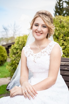 Closeup retrato de noiva feliz e sorridente, sentada no banco do parque