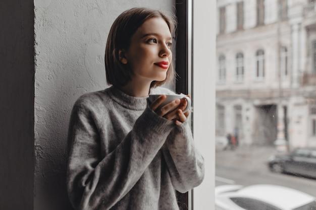 Closeup retrato de senhora de suéter de lã cinza com batom vermelho, desfrutando de chá perto da janela.