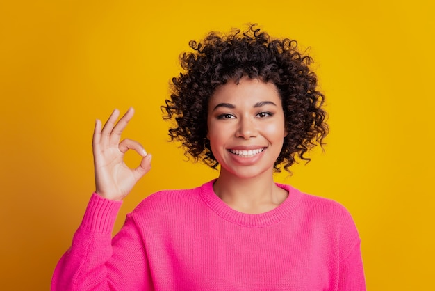 Closeup retrato de senhora mostrar sinal de ok isolado fundo de parede amarela