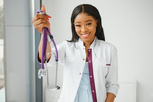 Closeup retrato de tiro na cabeça de profissional de saúde feminino confiante e sorridente, amigável, com jaleco, braços cruzados segurando os óculos. fundo de clínica hospitalar isolado. hora de uma visita ao escritório