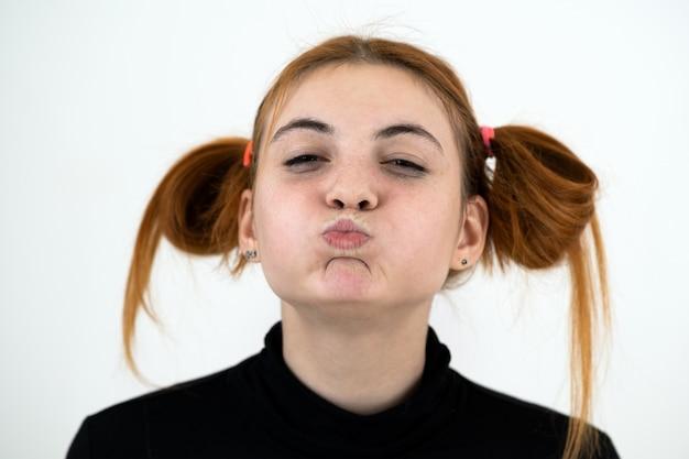 Closeup retrato de um adolescente ruiva engraçado com penteado infantil isolado no fundo branco.