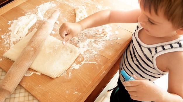 Closeup retrato de um adorável garoto de 3 anos rolando massa de trigo com rolo e cortando biscoitos com um cortador de plástico especial