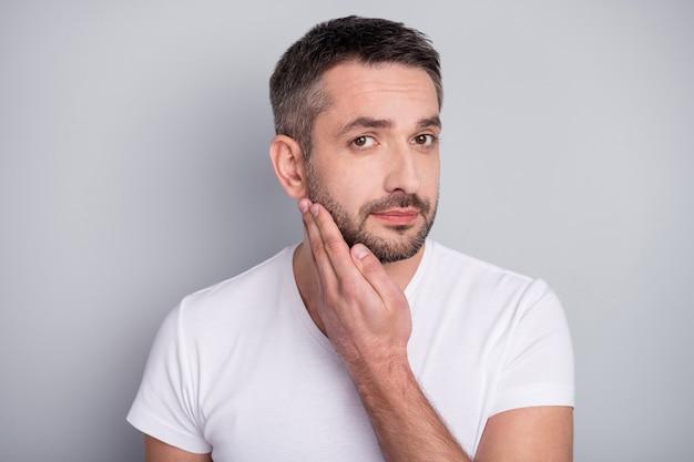 Closeup retrato de um cara atraente tocando uma cerda de cabelo com a barba por fazer