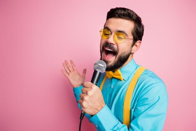 Closeup retrato de um cara barbudo cantando no karaokê segurando o microfone