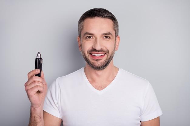 Closeup retrato de um cara bem preparado e alegre segurando um cortador de cabelo